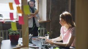 Il giovane studente biondo che indossa l'abbigliamento casual è occupato scrivere sul computer portatile mentre il suo amico è li video d archivio