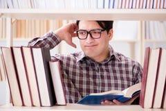 Il giovane studente che cerca i libri nella biblioteca di istituto universitario Fotografie Stock