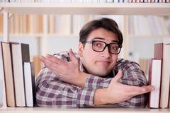 Il giovane studente che cerca i libri nella biblioteca di istituto universitario Immagini Stock