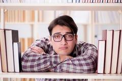 Il giovane studente che cerca i libri nella biblioteca di istituto universitario Fotografia Stock