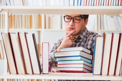 Il giovane studente che cerca i libri nella biblioteca di istituto universitario Fotografie Stock Libere da Diritti