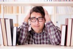 Il giovane studente che cerca i libri nella biblioteca di istituto universitario Fotografia Stock Libera da Diritti