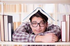 Il giovane studente che cerca i libri nella biblioteca di istituto universitario Immagine Stock Libera da Diritti