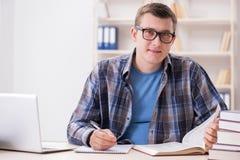 Il giovane studente che prepara agli esami della scuola con i libri Immagine Stock