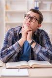 Il giovane studente che prepara agli esami della scuola con i libri Fotografie Stock