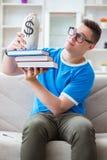 Il giovane studente che prepara per gli esami che studiano a casa su un sofà Fotografie Stock Libere da Diritti
