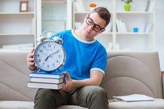 Il giovane studente che prepara per gli esami che studiano a casa su un sofà Fotografia Stock
