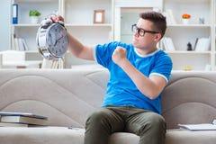 Il giovane studente che prepara per gli esami che studiano a casa su un sofà Fotografia Stock Libera da Diritti