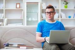 Il giovane studente che prepara per gli esami che studiano a casa su un sofà Immagine Stock