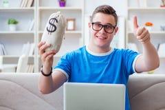 Il giovane studente che prepara per gli esami che studiano a casa su un sofà Immagini Stock