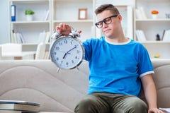 Il giovane studente che prepara per gli esami che studiano a casa su un sofà Immagini Stock Libere da Diritti