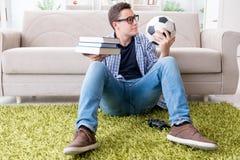 Il giovane studente che prova ad equilibrare studio e giocar a calcioe Immagine Stock Libera da Diritti
