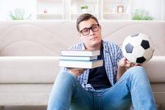 Il giovane studente che prova ad equilibrare studio e giocar a calcioe Immagine Stock