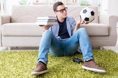 Il giovane studente che prova ad equilibrare studio e giocar a calcioe Fotografia Stock