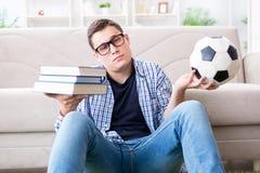 Il giovane studente che prova ad equilibrare studio e giocar a calcioe Fotografia Stock Libera da Diritti