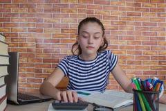 Il giovane studente che si siede fra i libri e calcola Studente, ragazza con le fatture e calcolatore nella stanza a casa Fotografie Stock