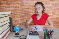 Il giovane studente che si siede fra i libri e calcola Studente, ragazza con le fatture e calcolatore nella stanza a casa Fotografie Stock Libere da Diritti