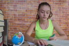 Il giovane studente che si siede fra i libri e calcola Studente, ragazza con le fatture e calcolatore nella stanza a casa Fotografia Stock Libera da Diritti