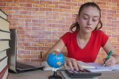 Il giovane studente che si siede fra i libri e calcola Studente, ragazza con le fatture e calcolatore nella stanza a casa Fotografia Stock