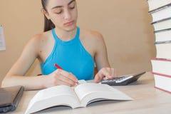 Il giovane studente che si siede fra i libri e calcola Ragazza con le fatture e calcolatore nel salone a casa Immagine Stock