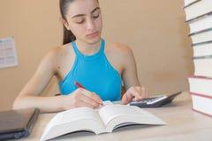 Il giovane studente che si siede fra i libri e calcola Ragazza con le fatture e calcolatore nel salone a casa Immagine Stock Libera da Diritti