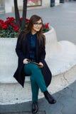 Il giovane studente che tiene un pc della compressa e si siede su un parapetto di marmo Fotografia Stock Libera da Diritti