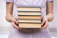Il giovane studente con la pila di libri Immagine Stock