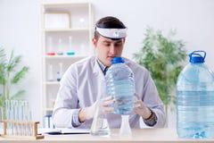 Il giovane studente del chimico che sperimenta nel laboratorio Immagine Stock