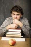 Il giovane studente emozionale con i libri e mela rossa nella stanza di classe Immagini Stock