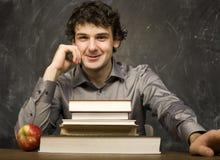 Il giovane studente emozionale con i libri e mela rossa nella stanza di classe Fotografie Stock Libere da Diritti