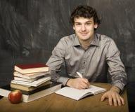 Il giovane studente emozionale con i libri e mela rossa nella stanza di classe Immagine Stock