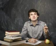 Il giovane studente emozionale con i libri e mela rossa nella stanza di classe Fotografie Stock