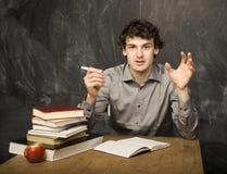 Il giovane studente emozionale con i libri e mela rossa nella stanza di classe Immagini Stock Libere da Diritti