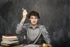 Il giovane studente emozionale con i libri e mela rossa nella stanza di classe Fotografia Stock
