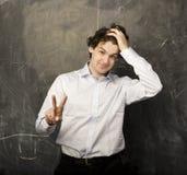 Il giovane studente emozionale nella stanza di classe alla lavagna Fotografia Stock Libera da Diritti