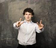 Il giovane studente emozionale nella stanza di classe alla lavagna Immagine Stock Libera da Diritti