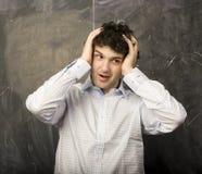 Il giovane studente emozionale nella stanza di classe alla lavagna Fotografie Stock Libere da Diritti