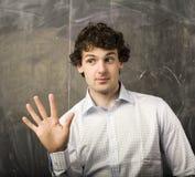 Il giovane studente emozionale nella stanza di classe alla lavagna Immagine Stock