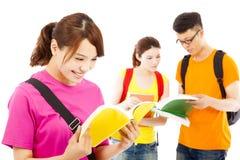 Il giovane studente ha letto un libro con i compagni di classe Fotografia Stock