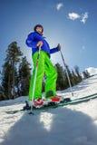 Il giovane su sci alpino sta su una pista nevosa contro il cielo Fotografia Stock Libera da Diritti