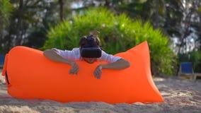 Il giovane su un sofà gonfiabile su una spiaggia tropicale usa i vetri di un VR Ritiene come sta nuotando in una sorveglianza del video d archivio