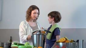 Il giovane succo d'arancia fresco casalingo caucasico del bambino e della madre e lo beve video d archivio