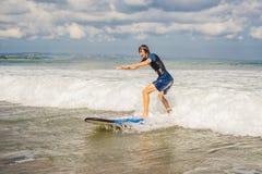 Il giovane, surfista del principiante impara praticare il surfing su una schiuma del mare sulla B immagini stock