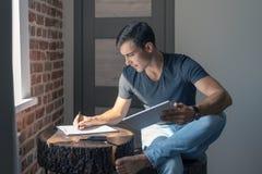Il giovane sveglio in maglietta e jeans ad una tavola di legno con una compressa, scrive in un taccuino, il business plan, indipe immagini stock libere da diritti