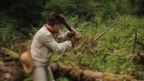 Il giovane taglialegna del connazionale nel ukrainain tradizionale copre lo spezzettamento del legno a pezzi della foresta verde  stock footage
