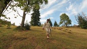 Il giovane taglialegna in vestiti ucraini tradizionali con l'ascia va a piedi nudi alla foresta stock footage