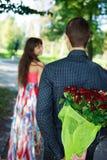 Il giovane tiene dietro sua la parte posteriore un mazzo del regalo delle rose rosse ciao Immagini Stock Libere da Diritti
