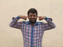 Il giovane tiene la mano sull'orecchio, uomo indiano che ha problema di udienza ascoltante qualcosa fotografia stock libera da diritti