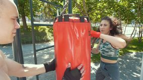 Il giovane tiene il punching ball alla donna atletica impegnata nel pugilato nel parco al giorno soleggiato, fine su video d archivio