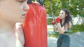 Il giovane tiene il punching ball alla donna atletica impegnata nel pugilato nel parco al giorno soleggiato, rallentatore video d archivio